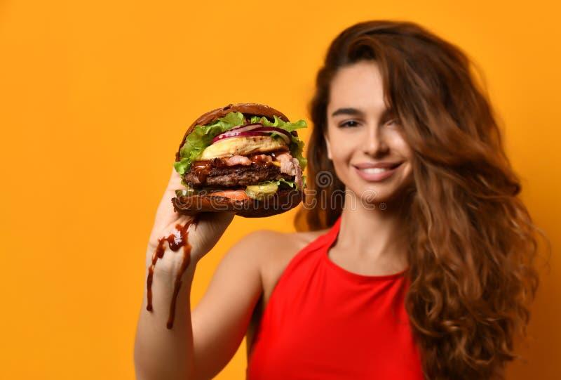 Van de de hamburgersandwich van de vrouwengreep de grote in hand hongerige mond die klaar te eten worden royalty-vrije stock foto