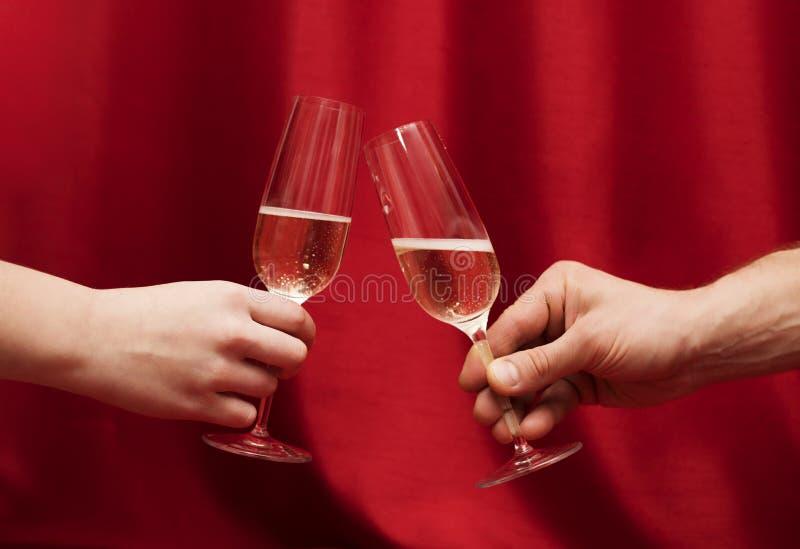 Van de handenman en vrouw zitting bij een lijst met glazen champagne stock foto