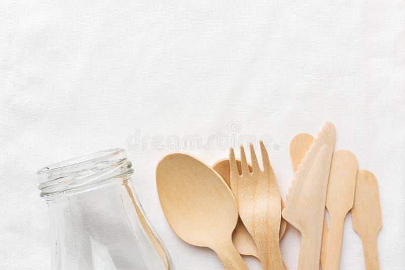 Van de het besteklepel van de glasfles houten de vorkmes op witte katoenen textielachtergrond Nul vriendschappelijke afval opnieu stock afbeeldingen
