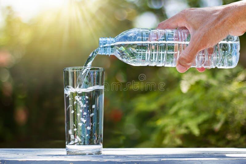 Van de het drinkwaterfles van de handholding het gietende water in glas op houten lijst stock foto