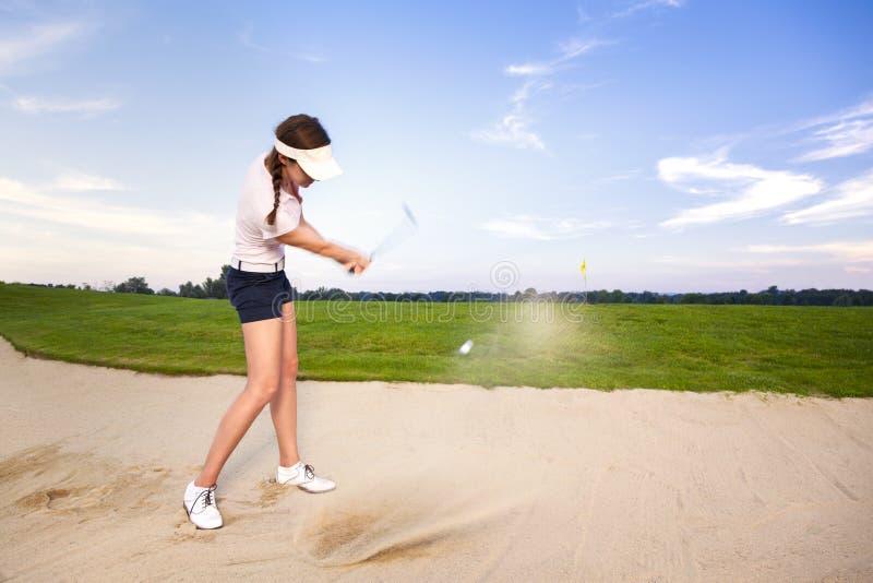 Van de het golfspeler van het meisje de scherfbal in bunker. stock foto