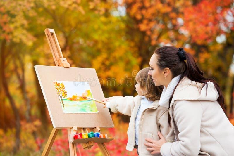 Van de van het de herfstaard, mamma en dochter de verf een beeld in een park van de herfst gaat weg, een weinig schilderend Kind, royalty-vrije stock foto