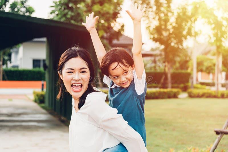 Van de het jonge geitjezoon van familie gelukkig kinderen van de de jongenskleuterschool van het de rit achtervervoer per kangoer royalty-vrije stock afbeelding