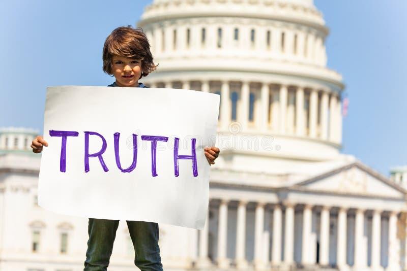 Van de het kindholding van de protesteerderjongen het teken veeleisende waarheid stock foto