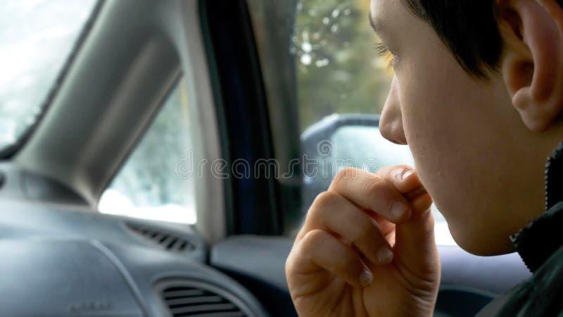 Van de het kindjongen van de close-upmening de handholding en het eten van koekjes terwijl het reizen in auto stock afbeeldingen