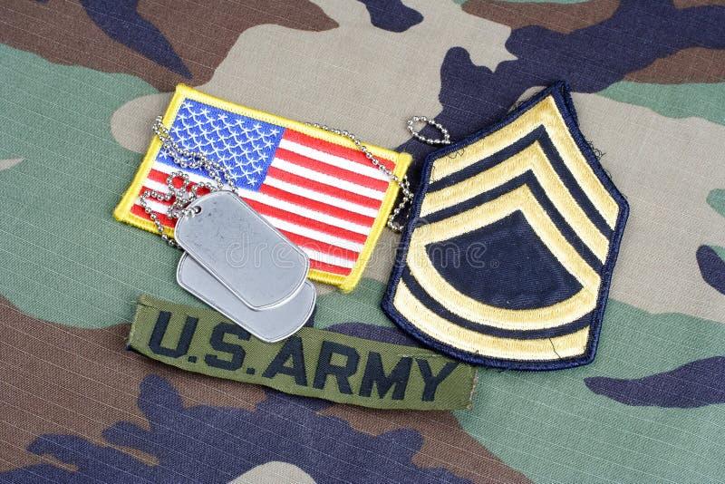 Van de het LEGERsergeant van de V.S. het weelderige flard van First Class, takband, vlagflard en hondmarkeringen op bos camouflag royalty-vrije stock foto's