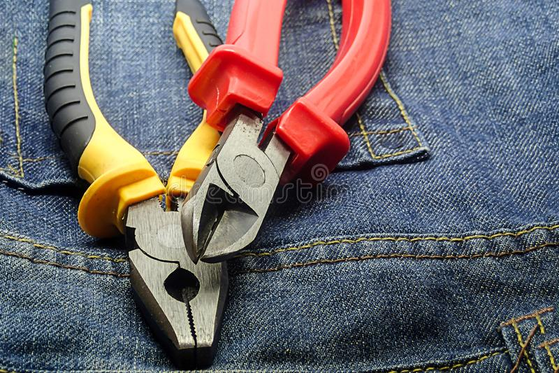 Van de het metaalbuigtang van de buigtangbuigtang de rubberreeks handhulpmiddelen die met elektriciteit aan een jeansachtergrond  stock foto's