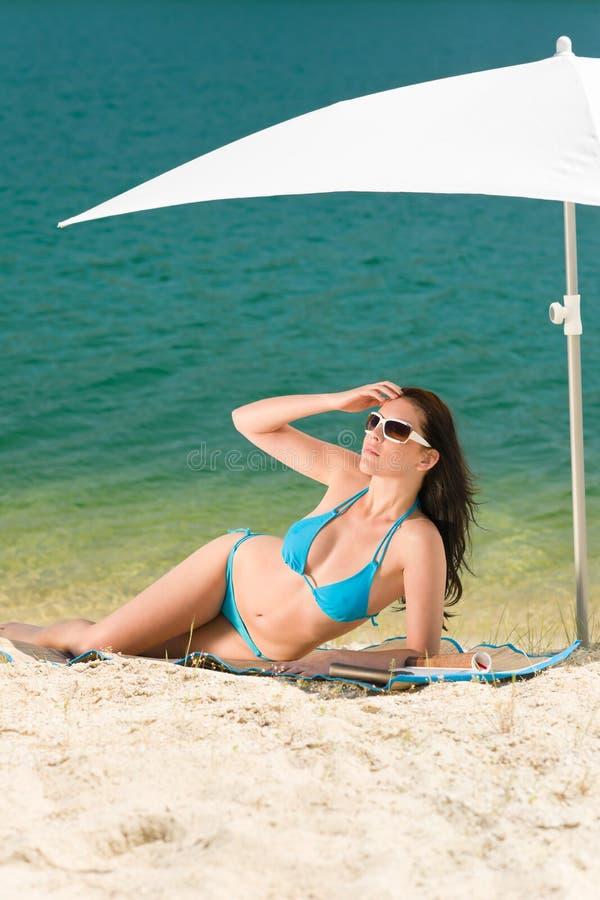 Van de het strandvrouw van de zomer de blauwe bikini onder parasol royalty-vrije stock foto