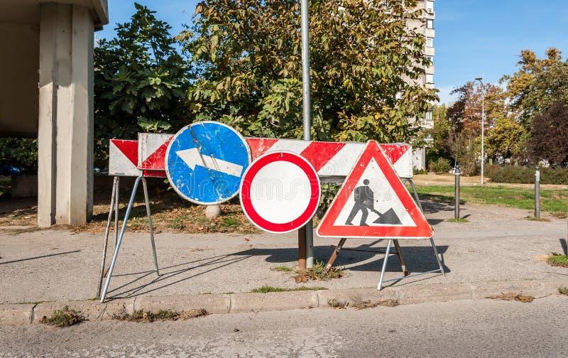 Van de het werk het waarschuwingsbord vooruit bouwwerf met wegbarricades en het verkeer waarschuwen barrières op de straat royalty-vrije stock afbeelding