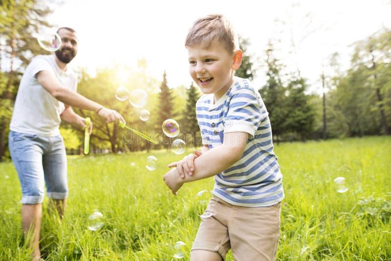 Van de Hipstervader en zoon blazende bellen in openlucht in park royalty-vrije stock fotografie