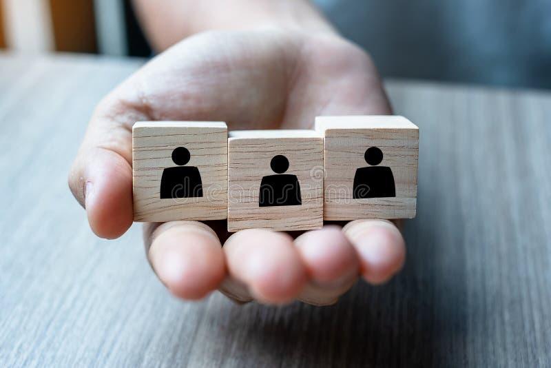 Van de de holdingspersoon van de zakenmanhand het houten blok op het gebouw Mensen, Zaken, Menselijk middelbeheer, Rekrutering, G royalty-vrije stock foto