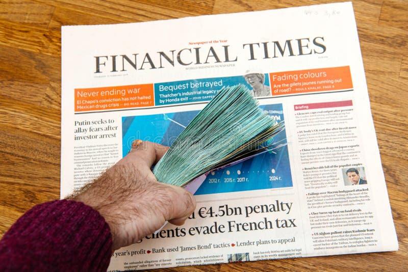 Van de de holdingsstapel van de mensenhand van het de stapelgeld de munt Financial Times royalty-vrije stock fotografie