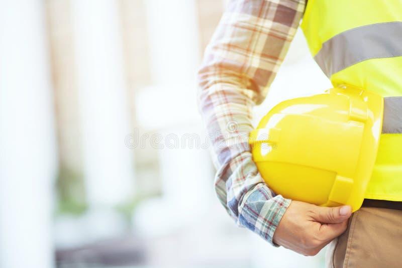 Van de de holdingsveiligheid van de techniek de mannelijke werktafel gele helm en slijtage weerspiegelende kleding stock afbeelding