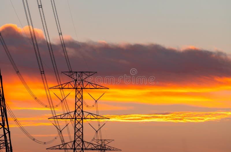 Van de hoogspannings elektrische pool en transmissie lijnen in de avond De pylonen van de elektriciteit bij zonsondergang Macht e royalty-vrije stock foto's