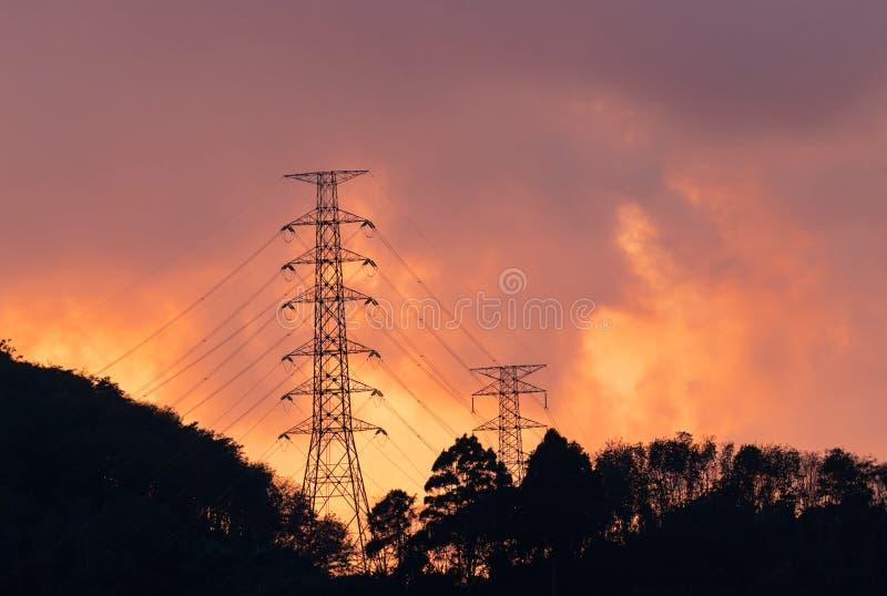Van de hoogspannings elektrische pool en transmissie lijnen in de avond De pylonen van de elektriciteit bij zonsondergang Macht e stock fotografie