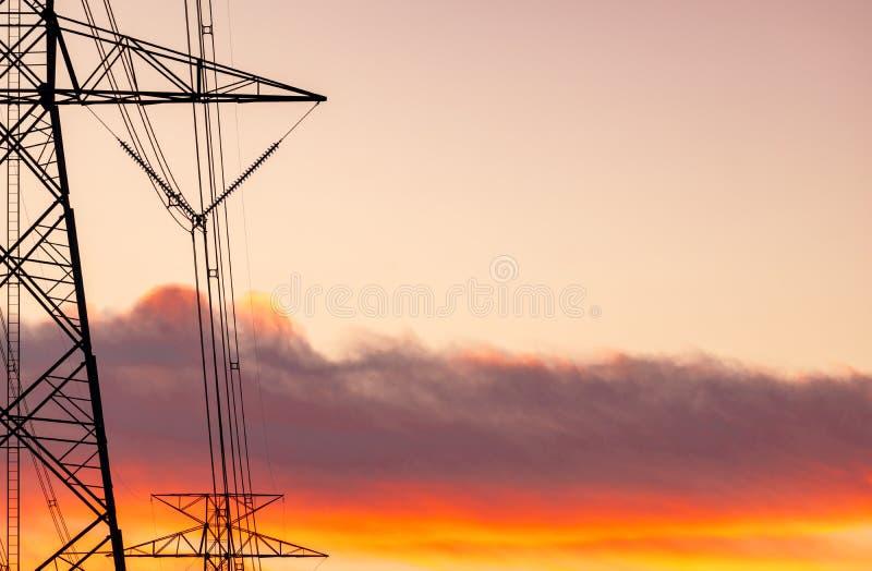 Van de hoogspannings elektrische pool en transmissie lijnen Elektriciteitspylonen bij zonsondergang met oranje hemel Macht en ene royalty-vrije stock afbeeldingen