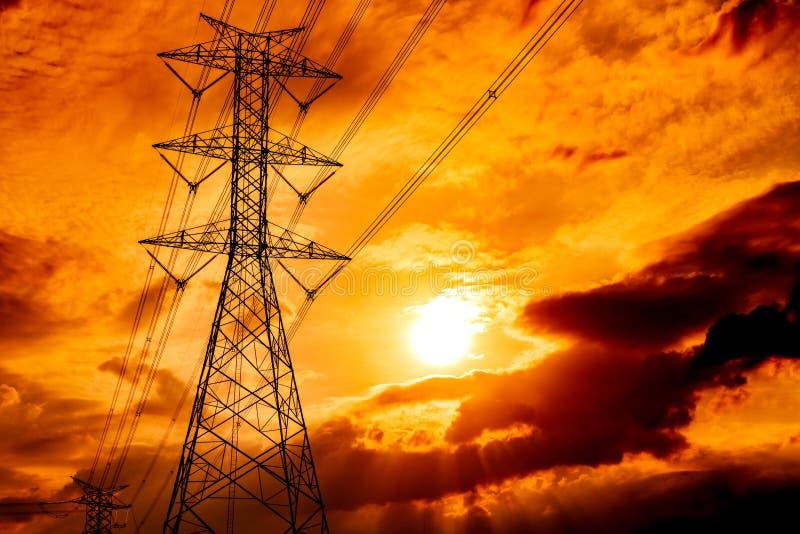 Van de hoogspannings elektrische pool en transmissie lijnen De pylonen van de elektriciteit bij zonsondergang Macht en energie He stock foto
