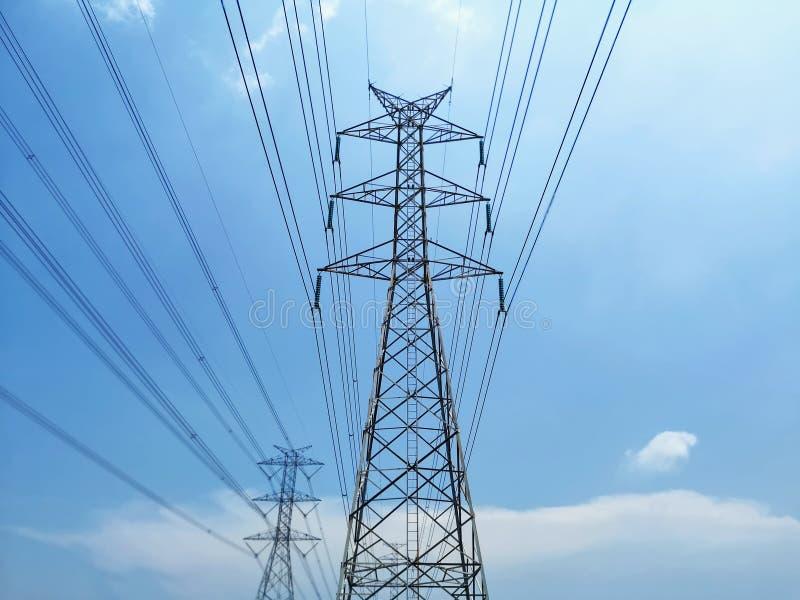Van de hoogspanningstoren en Macht Lijnen tegen Blauwe Bewolkte Hemel stock foto's