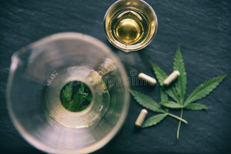 Van de de installatiecannabis van het marihuanablad het aftreksel en de capsule op donkere bladeren als achtergrond/Hennep voor n stock foto's