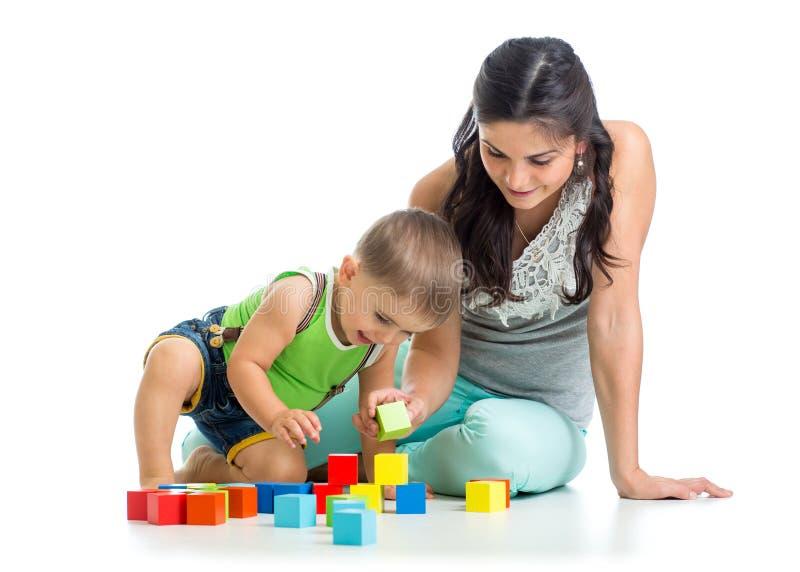 Van de jong geitjejongen en moeder spel samen met blokspeelgoed stock afbeeldingen