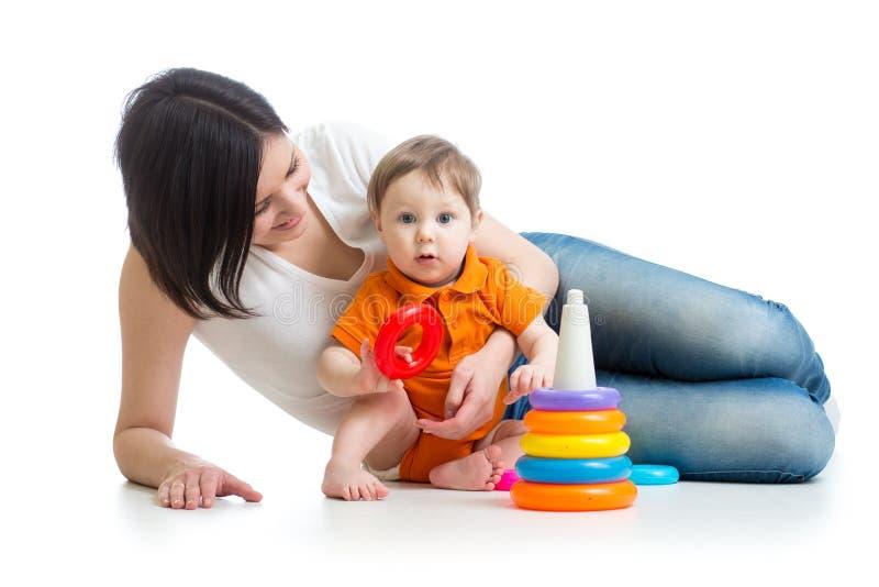 Van de jong geitjejongen en moeder spel samen met piramidestuk speelgoed royalty-vrije stock foto