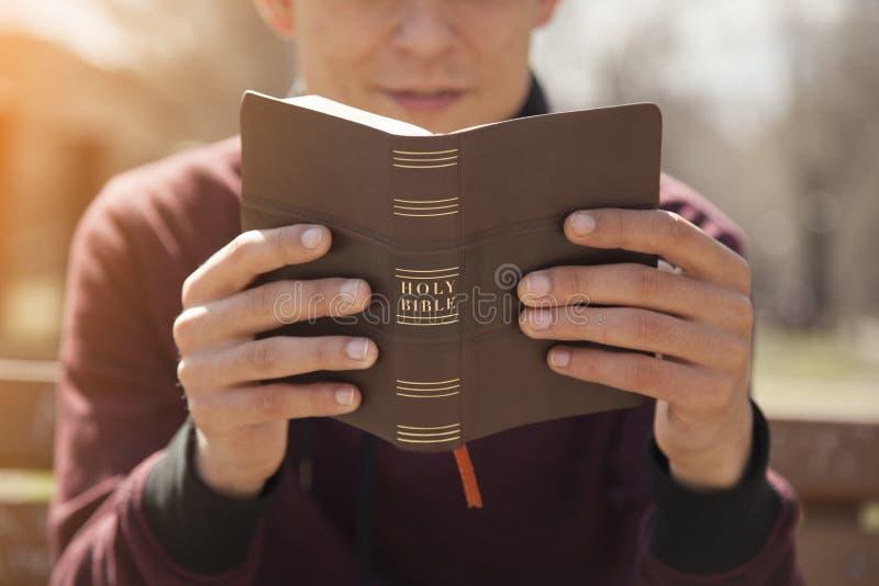 Van de jonge mensenholding en lezing heilige bijbel royalty-vrije stock afbeeldingen