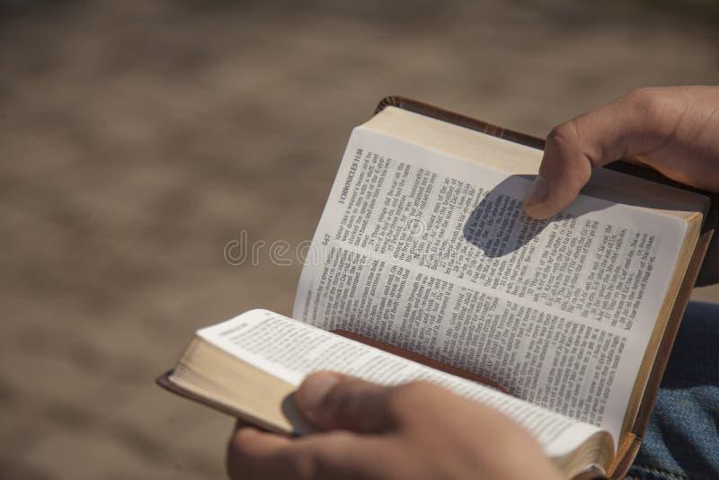 Van de jonge mensenholding en lezing heilige bijbel stock afbeelding