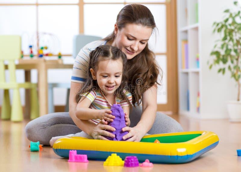 Van de kindmeisje en vrouw vorm met kinetisch zand in playschool of opvang royalty-vrije stock foto