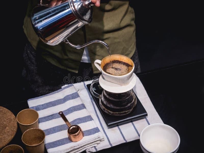 Van de koffiebarista van de handdruppel het gietende water op koffiedik royalty-vrije stock afbeelding