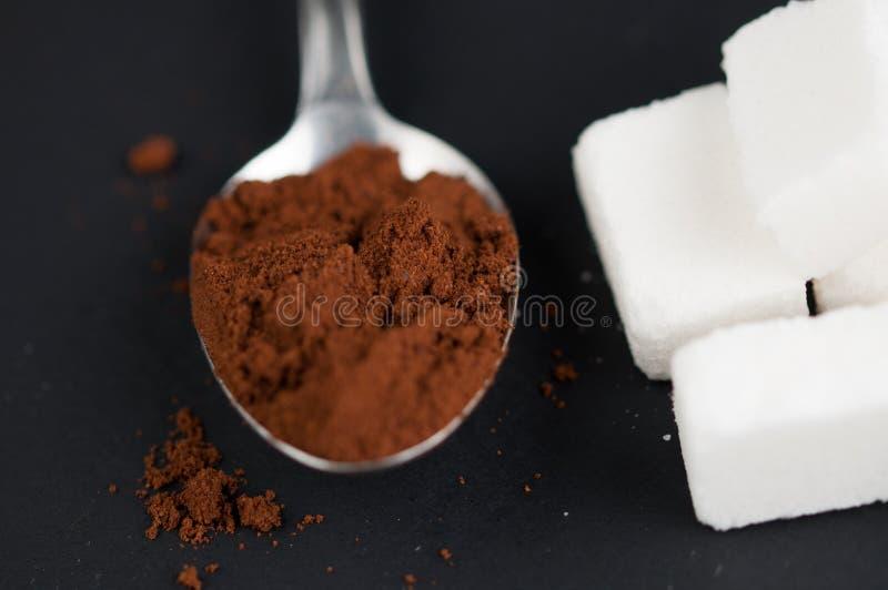 Van de koffielepel en suiker kubussen op een zwarte achtergrond worden geïsoleerd die stock foto's