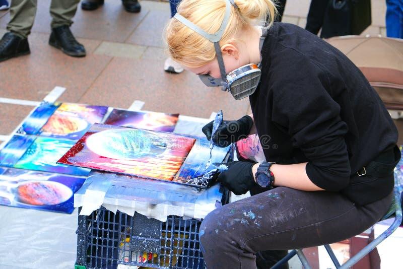 Van de kunstenaarsYoung van de meisjesstraat het mooie blonde Straatkunst in het proces, straat kunstenaar-schilder Heilige-Peter stock afbeeldingen