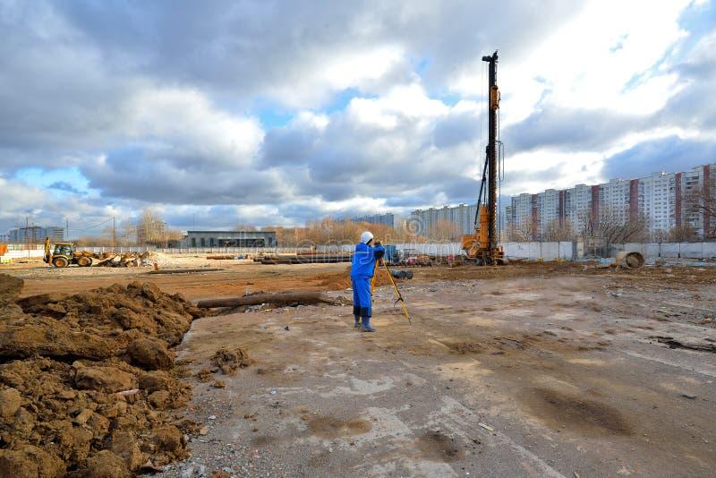 Van de landmetersarbeider en bouw machines op een bouwwerf royalty-vrije stock foto's
