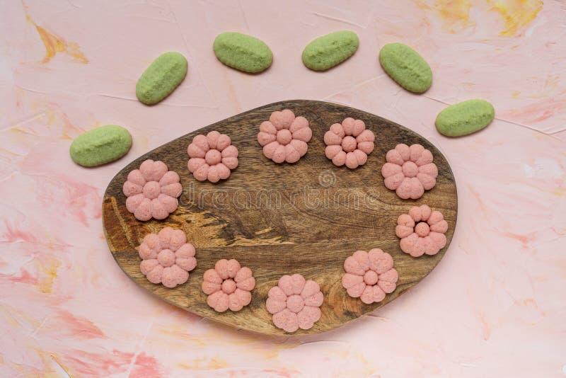 Van de de LENTEwoord en bloem koekjes op een houten raad op een roze achtergrond De lentevakantie die concept koken royalty-vrije stock fotografie