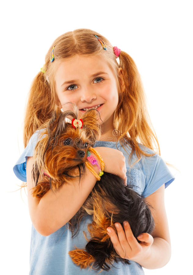 Van de meisjeglimlach en greep leuke kleine hond stock fotografie