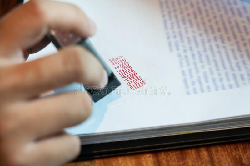 Van de de notarishand van zakenmanHand de inkt gaat de appoval stamper het Stempelen verbinding op de Goedgekeurde documenten van stock foto