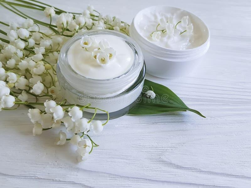 Van de de ontspanningszalf van het room de kosmetische lelietje-van-dalen aromatische rustieke schoonheid op een witte houten ach royalty-vrije stock foto's