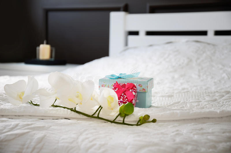 Van de orchideebloem en gift dozen op het bed in de slaapkamer horizont royalty-vrije stock afbeeldingen