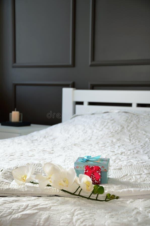 Van de orchideebloem en gift dozen op het bed in de slaapkamer verticaal royalty-vrije stock foto