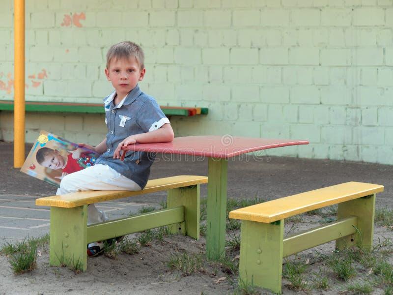 6 van de oude jongensjaar zitting op een bank stock foto's