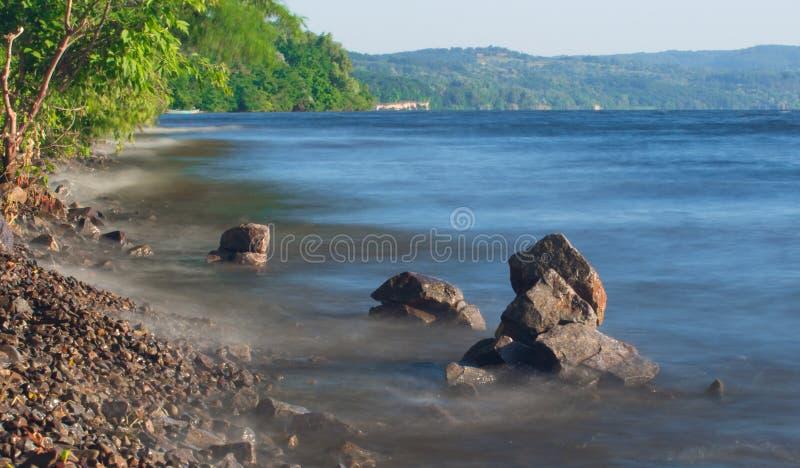 Van de overzeese de rots van het de lijneffect golvenzweep op het strand stock fotografie