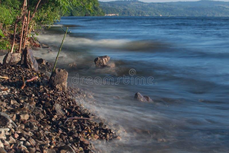 Van de overzeese de rots van het de lijneffect golvenzweep op het strand stock afbeelding