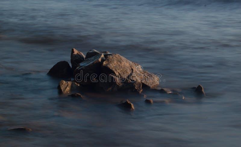 Van de overzeese de rots van het de lijneffect golvenzweep op het strand stock foto's