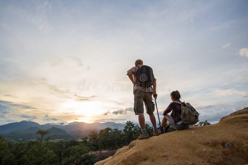 Van de paarman en Vrouw zitting op klip die van bergen, Reis genieten stock foto's