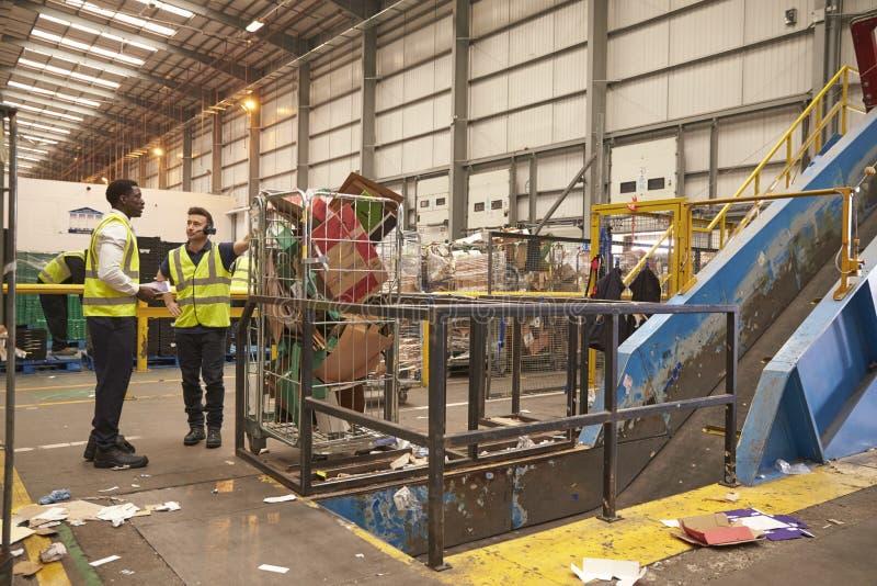 Van de pakhuismanager en collega bespreking door machines te recycleren stock fotografie