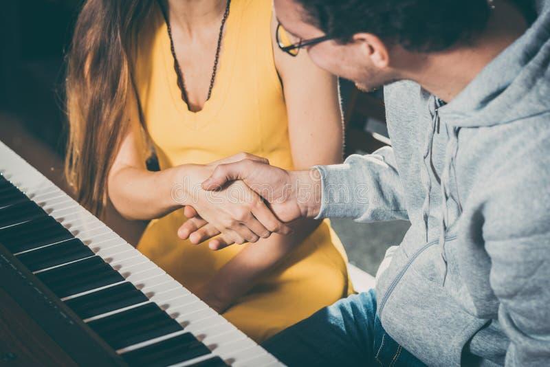 Van de pianoleraar en student het schudden handen na les stock afbeeldingen