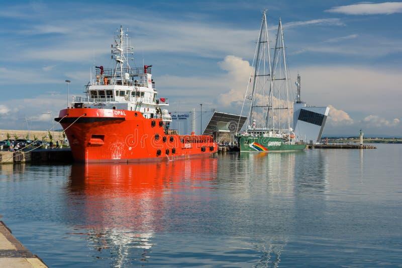 Van de de Regenboogstrijder van Greenpeace het varend schip en Opal Valletta Offshore Supply Ship bij de Haven van Burgas, Bulgar stock foto