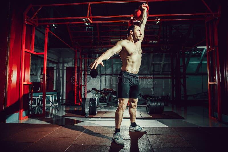 Van de de schommelingsoefening van geschiktheidskettlebells de mensentraining bij gymnastiek royalty-vrije stock afbeelding