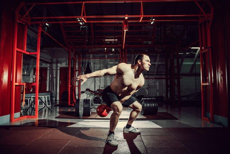 Van de de schommelingsoefening van geschiktheidskettlebells de mensentraining bij gymnastiek stock afbeelding