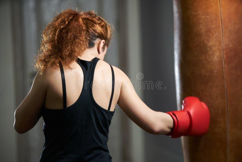 Van de de slijtage bokshandschoen van de sportvrouw de schopbokser in de gymnastiek stock foto's