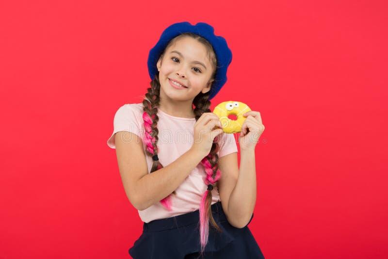 Van de snoepjeswinkel en bakkerij concept Jong geitjeventilator van gebakken donuts Heerlijke Zoete Doughnut Meisje in het rood v stock foto's